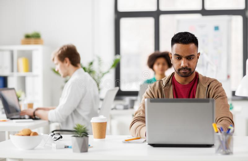 Ινδικό άτομο με το φορητό προσωπικό υπολογιστή στο γραφείο στοκ εικόνες