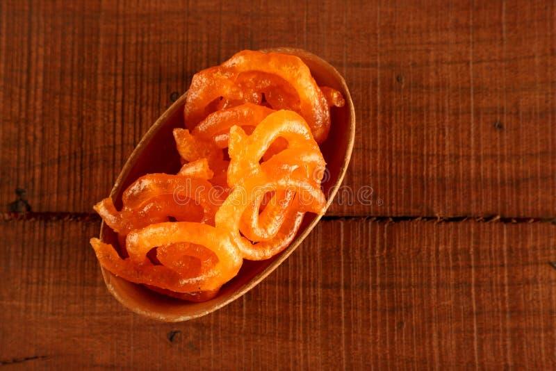 Ινδικό γλυκό Τζαλεμπί σε χειροποίητο μπολ κεραμικής σε ξύλινο φόντο στοκ εικόνες