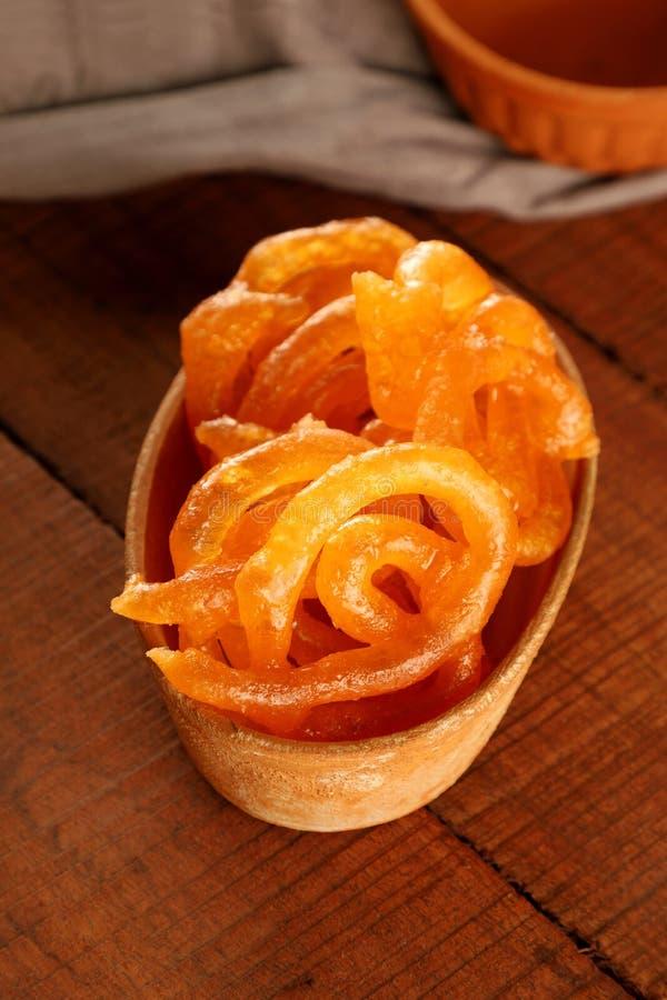 Ινδικό γλυκό Τζαλεμπί σε χειροποίητο μπολ κεραμικής σε ξύλινο φόντο στοκ εικόνα