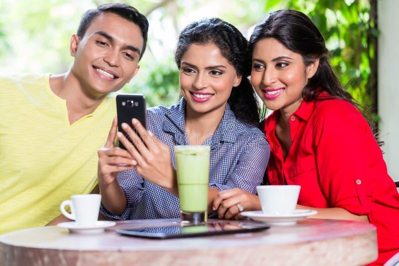 Ινδικό κορίτσι που παρουσιάζει εικόνες στο τηλέφωνο στους φίλους στοκ εικόνα με δικαίωμα ελεύθερης χρήσης