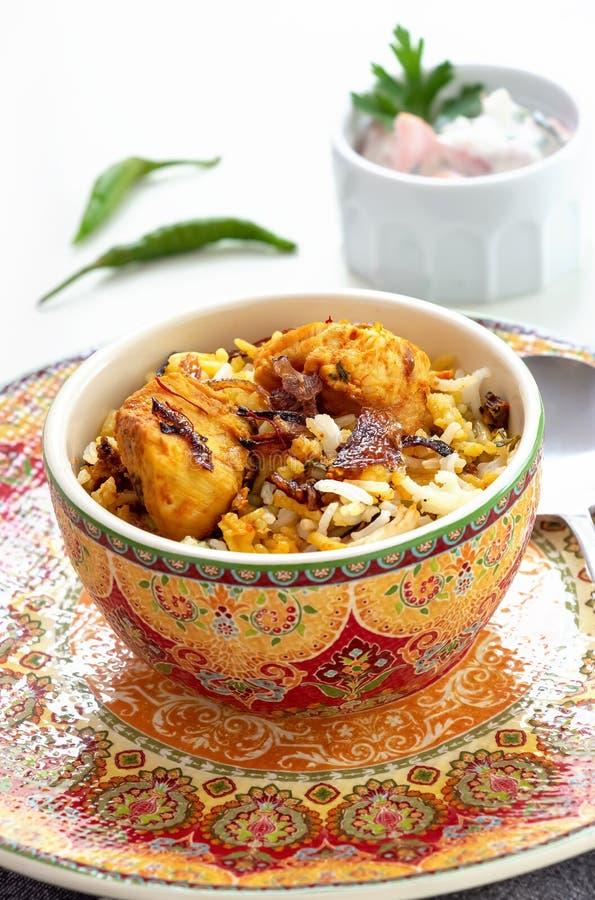 Ινδικό κοτόπουλο Biryani Halal που εξυπηρετείται με το raita ντοματών γιαουρτιού πέρα από το άσπρο υπόβαθρο r στοκ φωτογραφίες
