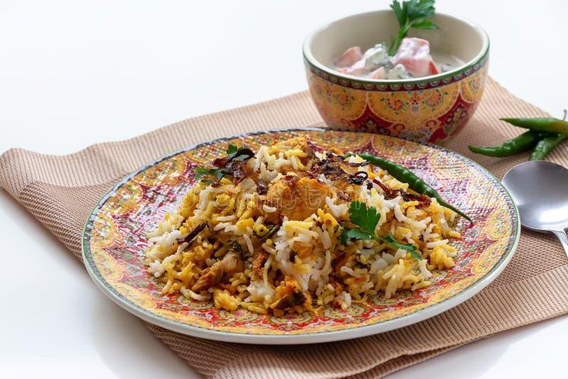 Ινδικό κοτόπουλο Biryani Halal που εξυπηρετείται με το raita ντοματών γιαουρτιού πέρα από το άσπρο υπόβαθρο r στοκ εικόνες με δικαίωμα ελεύθερης χρήσης