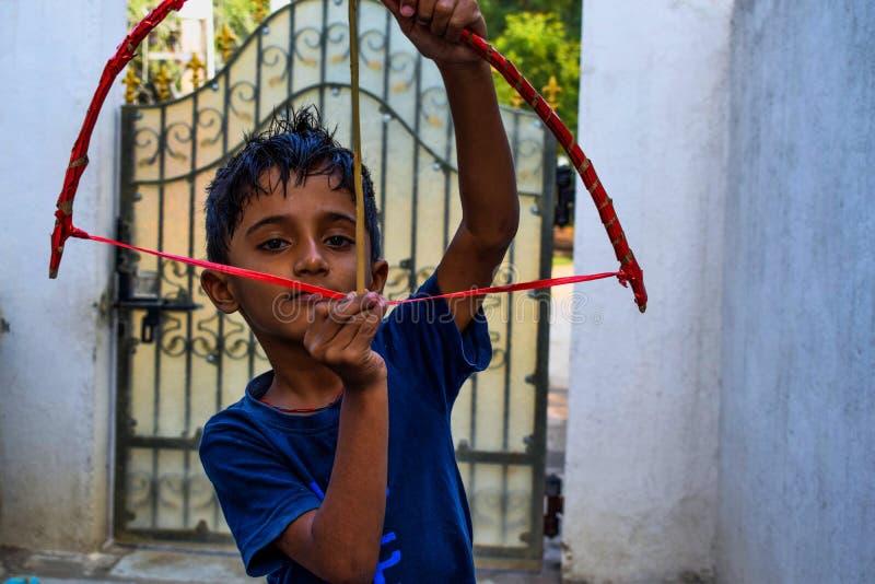 Ινδικό παιχνίδι παιδιών με το τόξο και το βέλος του στο σπίτι στοκ εικόνα