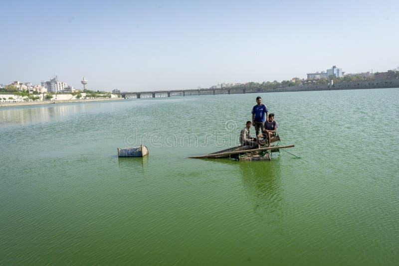 Ινδοί άνθρωποι που διασχίζουν τον ποταμό στα κομμάτια του ξύλου στοκ φωτογραφίες