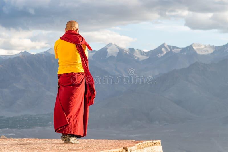 Ινδός & x28 tibetan& x29  λάμα μοναχών στον κόκκινο και κίτρινο ιματισμό χρώματος που στέκεται μπροστά από τα βουνά στοκ εικόνα