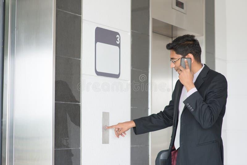 Ινδικός επιχειρηματίας που εισάγει τον ανελκυστήρα στοκ φωτογραφίες