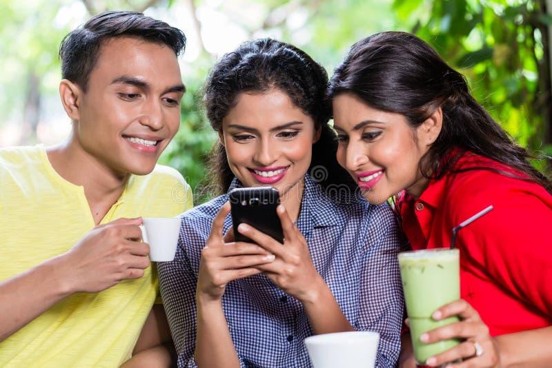 Ινδικό κορίτσι που παρουσιάζει εικόνες στο τηλέφωνο στους φίλους στοκ εικόνα