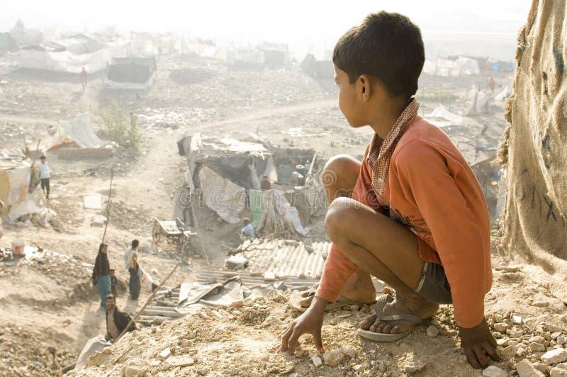 Ινδικό παιδί σε μια τρώγλη στο Δελχί, Ινδία 19/07/2012 στοκ εικόνα