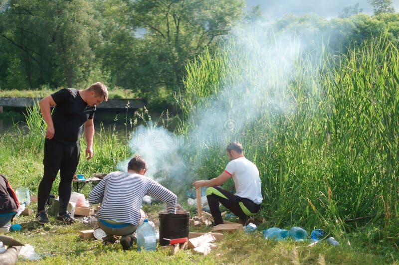 12 Ιουνίου 2018, περιοχή Kaliningrad, της Ρωσίας, ταξιδιώτες πυρών προσκόπων στη λίμνη, μάγειρας τουριστών στην πυρά προσκόπων στοκ φωτογραφία με δικαίωμα ελεύθερης χρήσης