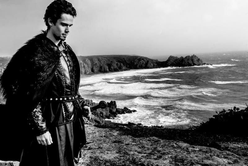 Ιππότης με δερμάτινη στολή, μανδύα για γούνα και σπαθί που στέκονται σε περισυλλογή στην κορυφή του γκρεμού με ωκεανούς στο παρασ στοκ φωτογραφίες