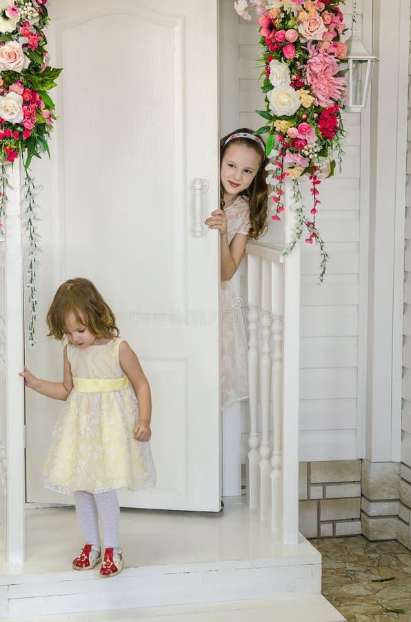 Ιρκούτσκ, Ρωσία - το Φεβρουάριο του 2017 μικρά χαριτωμένα κορίτσια κοντά στην πόρτα με τα λουλούδια στοκ εικόνες