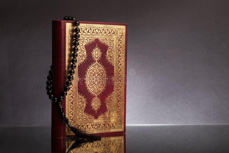 Ισλαμικό βιβλίο Koran με rosary στο γκρίζο υπόβαθρο στοκ εικόνες με δικαίωμα ελεύθερης χρήσης