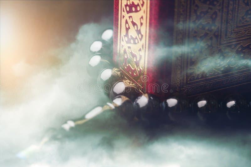 Ισλαμικό βιβλίο Koran με rosary στο γκρι στοκ φωτογραφία