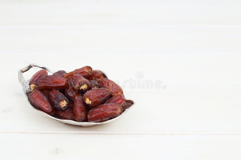 Ισλαμικό φεστιβάλ της έννοιας Ramadan με εύγευστες τροπικές ημερομηνίες σε ένα ασημένιο πιάτο και λαμπρό rosary σε ένα άσπρο ξύλι στοκ φωτογραφία με δικαίωμα ελεύθερης χρήσης