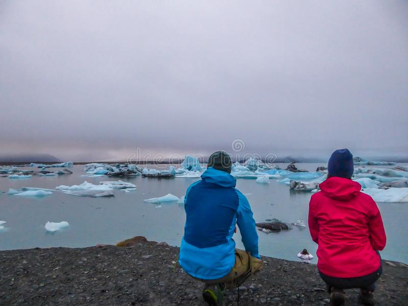 Ισλανδία - ένα ζεύγος που κάθεται οκλαδόν στην άκρη ενός απότομου βράχου, που εξετάζει τη λιμνοθάλασσα παγετώνων στοκ εικόνες