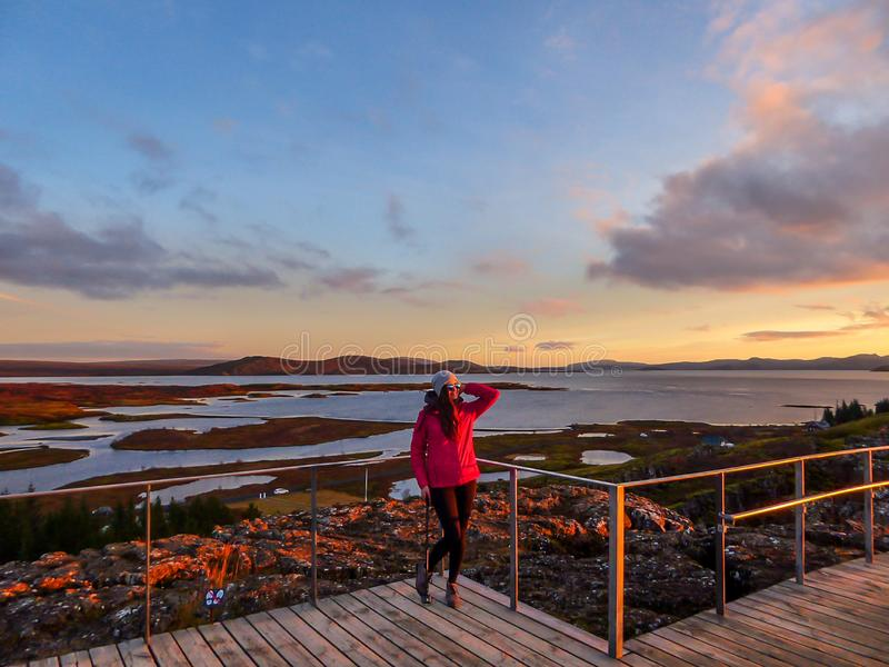 Ισλανδία - ένα κορίτσι που απολαμβάνει τις τελευταίες ακτίνες ήλιων της ημέρας στο εθνικό πάρκο Pingvellir στοκ εικόνα
