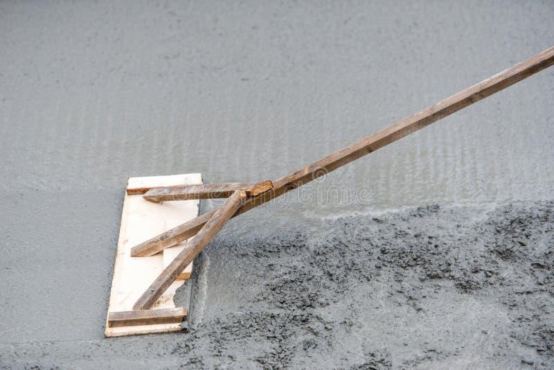Ισοπέδωση εργαζομένων με το ανώμαλο φρέσκο σκυρόδεμα trowel στην οικοδόμηση στοκ εικόνα με δικαίωμα ελεύθερης χρήσης
