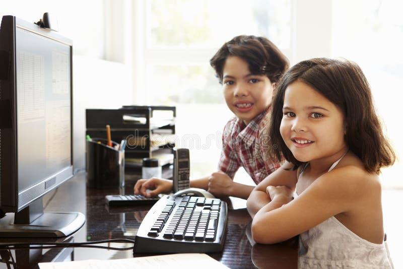 Ισπανικά παιδιά που χρησιμοποιούν τον υπολογιστή στο σπίτι στοκ εικόνες