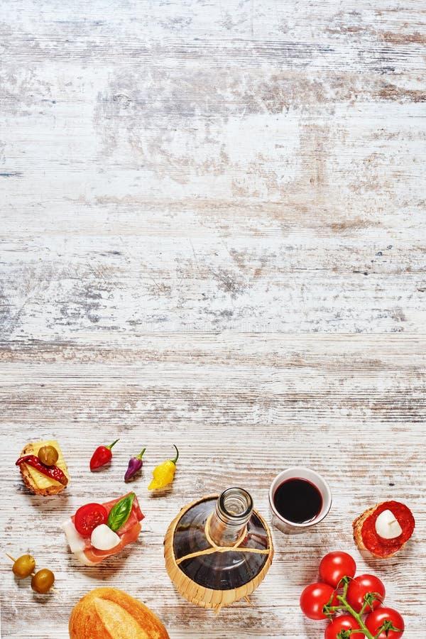 Ισπανικά tapas και μπουκάλι του κόκκινου κρασιού σε έναν ξύλινο πίνακα στοκ φωτογραφία με δικαίωμα ελεύθερης χρήσης