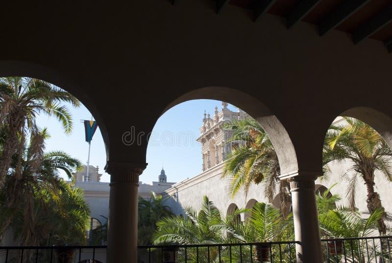 Ισπανική αρχιτεκτονική Άποψη μέσω των αψίδων του παλατιού στον κήπο φοινικών σε μια ηλιόλουστη ημέρα στοκ εικόνα με δικαίωμα ελεύθερης χρήσης