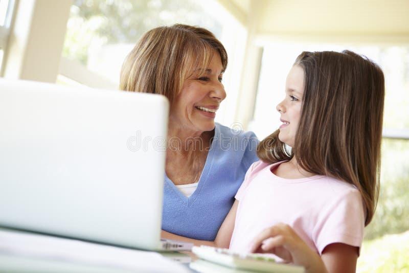 Ισπανική γιαγιά που χρησιμοποιεί το lap-top και τον υπολογιστή με Granddaugh στοκ εικόνα