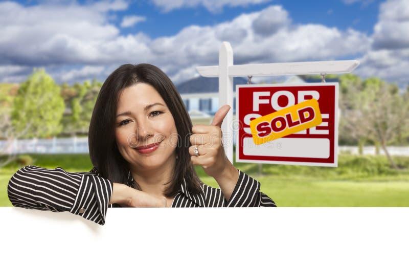Ισπανική γυναίκα μπροστά από πωλημένος για το σημάδι πώλησης, σπίτι στοκ εικόνα με δικαίωμα ελεύθερης χρήσης