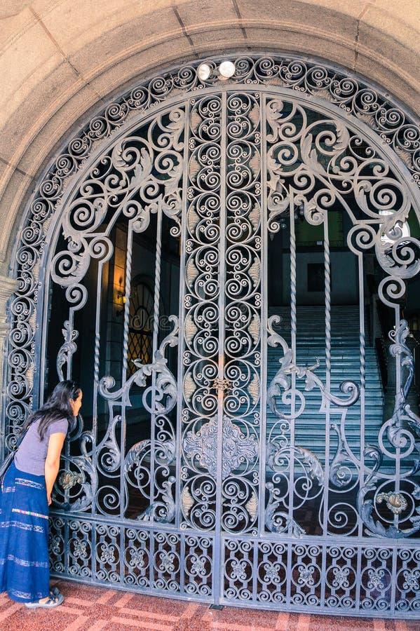 Ισπανική γυναίκα που κοιτάζει μέσω της πύλης στοκ εικόνες