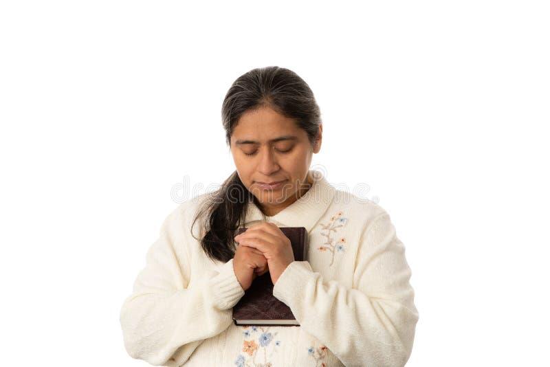 Ισπανική γυναίκα που προσεύχεται ενώ Βίβλος εκμετάλλευσης στο άσπρο υπόβαθρο στοκ εικόνες