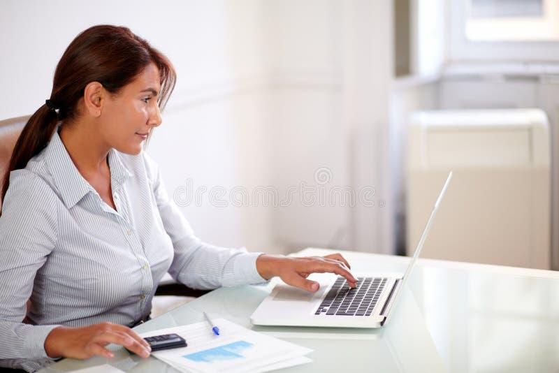Ισπανική επιχειρηματίας που εργάζεται με το lap-top της στοκ εικόνες