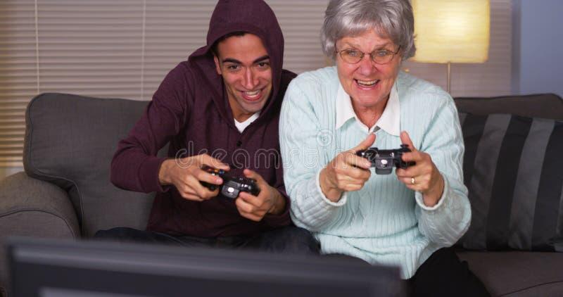 Ισπανικοί εγγονός και γιαγιά που παίζουν τα τηλεοπτικά παιχνίδια στοκ φωτογραφία με δικαίωμα ελεύθερης χρήσης