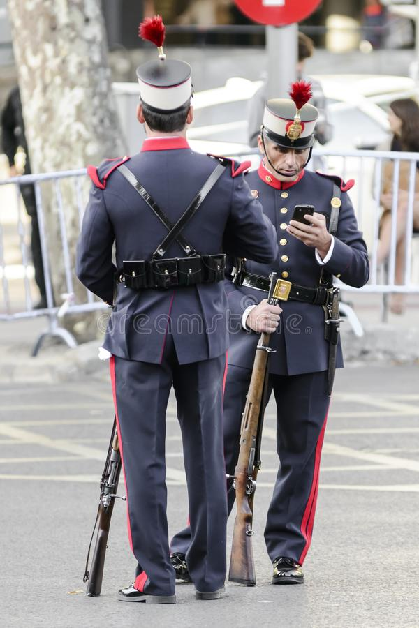 Ισπανικός βασιλικός στρατιώτης φρουράς που εξετάζει το κινητό τηλέφωνό του στοκ φωτογραφίες