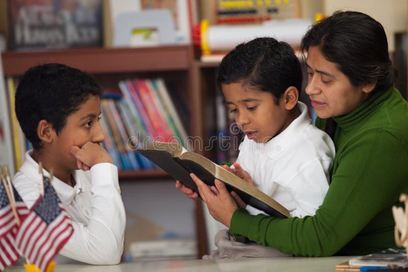 Ισπανικό αγόρι που διαβάζει τη Βίβλο κατά τη διάρκεια της οικογενειακής λατρείας στοκ φωτογραφίες