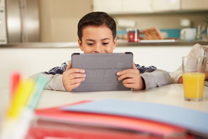 Ισπανικό αγόρι που κάνει την εργασία στον πίνακα που χρησιμοποιεί την ψηφιακή ταμπλέτα στοκ εικόνα με δικαίωμα ελεύθερης χρήσης