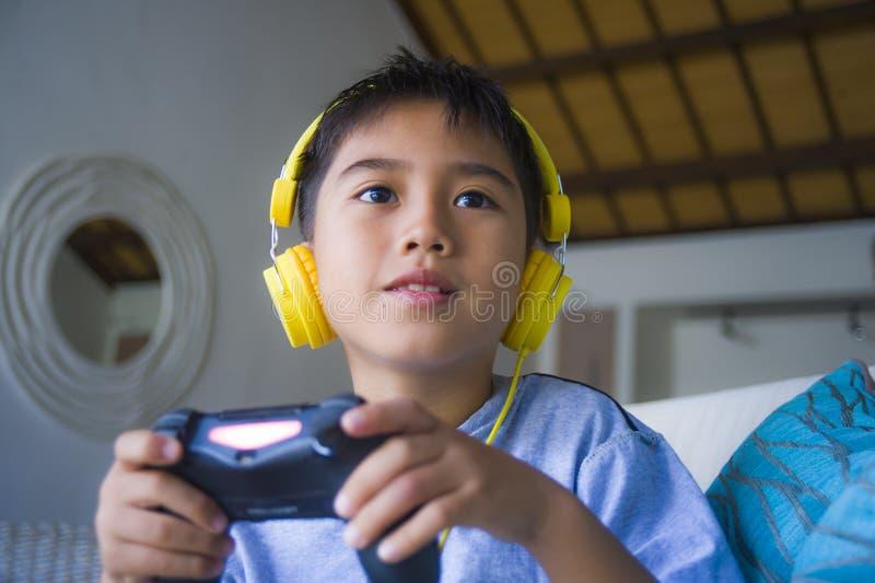 Ισπανικό παιδάκι Oung συγκινημένο και ευτυχές τηλεοπτικό παιχνίδι παιχνιδιού on-line με τα ακουστικά που κρατά τον ελεγκτή απολαμ στοκ εικόνες με δικαίωμα ελεύθερης χρήσης