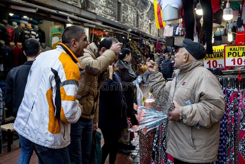 ΙΣΤΑΝΜΠΟΎΛ, ΤΟΥΡΚΙΑ - 28 ΔΕΚΕΜΒΡΊΟΥ 2015: Παλαιός έμπορος που προσπαθεί να πωλήσει τις επικεφαλής συσκευές μασάζ αντι πίεσης στα  στοκ φωτογραφία με δικαίωμα ελεύθερης χρήσης