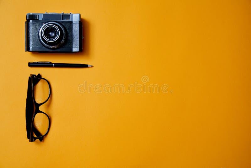 Ιστολόγιο, ιστολόγιο και blogger ή ιδέα μέσων κοινωνικής δικτύωσης: γυαλιά, φωτογραφική μηχανή και ένα στυλό στο κίτρινο φόντο Επ στοκ φωτογραφίες