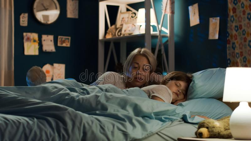 Ιστορία αφήγησης γυναικών στο κορίτσι στο κρεβάτι στοκ φωτογραφία με δικαίωμα ελεύθερης χρήσης