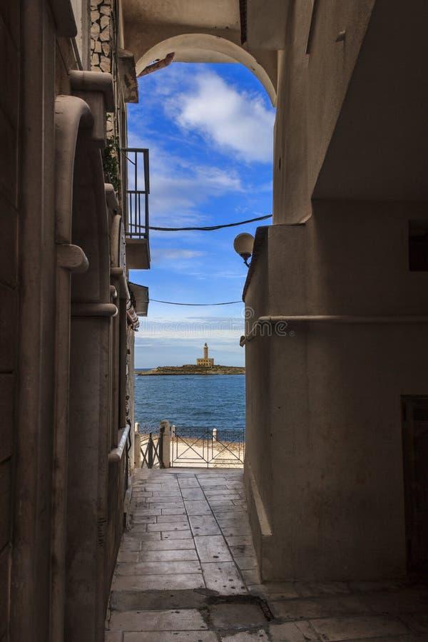 Ιστορικό κέντρο Vieste ` s: άποψη του φάρου από ένα arcade στο λιμάνι ` Βρίσκεται στο νησάκι Santa Eufemia στοκ εικόνα με δικαίωμα ελεύθερης χρήσης
