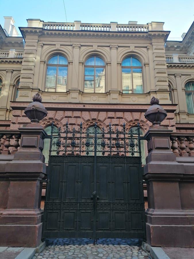 Ιστορικό κτήριο με τις διακοσμήσεις και φράκτης με τις πύλες επεξεργασμένου σιδήρου στοκ εικόνα