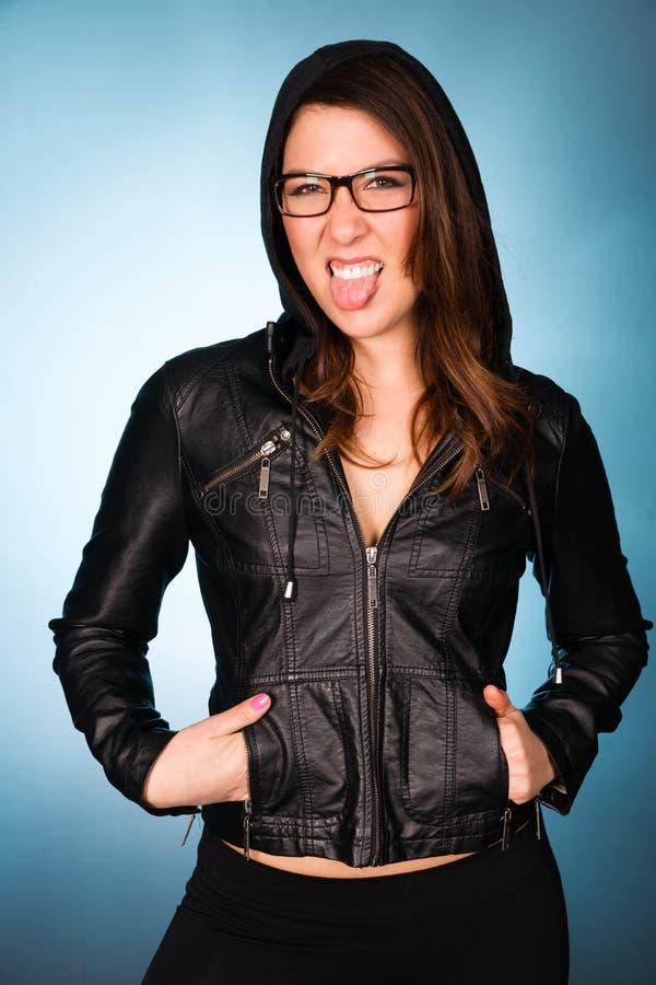 Ισχίο που χαμογελά τη νέα ενήλικη γυναίκα που φορά τη με κουκούλα μπλούζα σακακιών δέρματος στοκ φωτογραφία με δικαίωμα ελεύθερης χρήσης