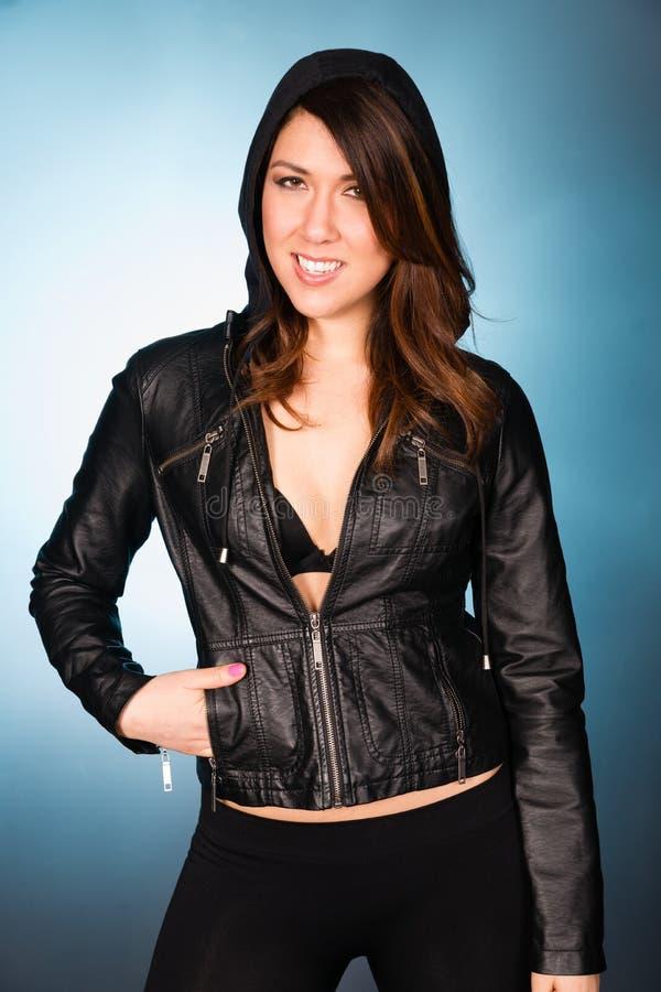 Ισχίο που χαμογελά τη νέα ενήλικη γυναίκα που φορά το σακάκι με κουκούλα Swea δέρματος στοκ φωτογραφίες