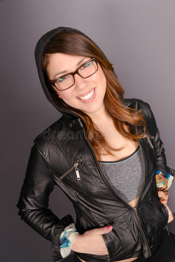 Ισχίο που χαμογελά τη νέα ενήλικη γυναίκα που φορά το σακάκι με κουκούλα Swea δέρματος στοκ φωτογραφίες με δικαίωμα ελεύθερης χρήσης
