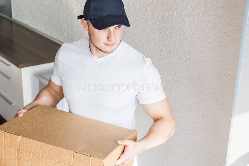 Ισχυρά, μυϊκά κουτιά από χαρτόνι φόρτωσης ατόμων παράδοσης για την κίνηση προς ένα διαμέρισμα επαγγελματικός εργαζόμενος της μετα στοκ εικόνα
