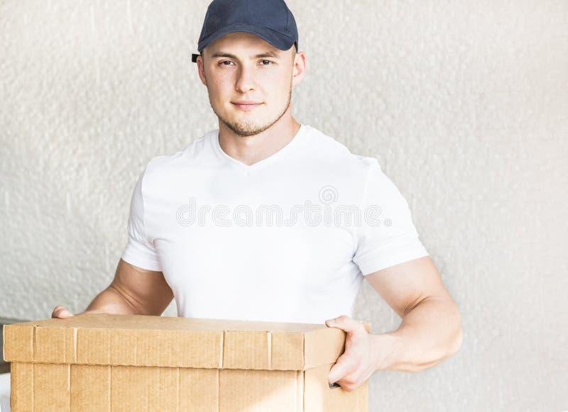 Ισχυρά, μυϊκά κουτιά από χαρτόνι φόρτωσης ατόμων παράδοσης για την κίνηση προς ένα διαμέρισμα επαγγελματικός εργαζόμενος της μετα στοκ φωτογραφίες