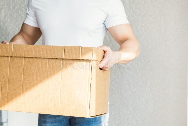 Ισχυρά, μυϊκά κουτιά από χαρτόνι φόρτωσης ατόμων παράδοσης για την κίνηση προς ένα διαμέρισμα επαγγελματικός εργαζόμενος της μετα στοκ εικόνες
