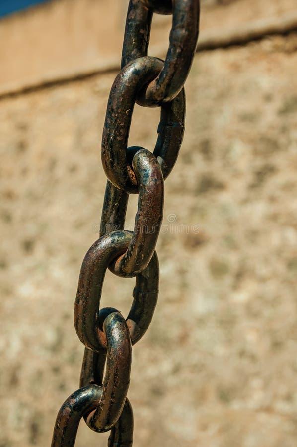 Ισχυρές συνδέσεις αλυσίδων σιδήρου μπροστά από τον τοίχο πετρών στοκ φωτογραφία με δικαίωμα ελεύθερης χρήσης