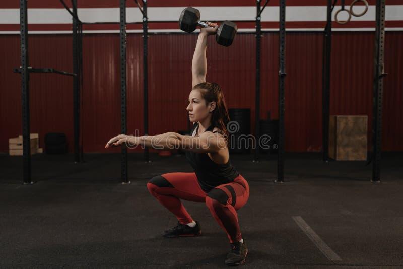 Ισχυρή αθλήτρια που κάνει τις στάσεις οκλαδόν αλτήρων Θηλυκά βάρη ανύψωσης αθλητών Crossfit στοκ φωτογραφίες με δικαίωμα ελεύθερης χρήσης