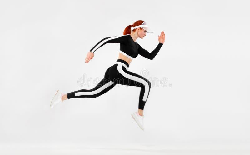 Ισχυρή αθλητική γυναίκα sprinter, τρέχοντας στο άσπρο υπόβαθρο που φορά sportswears Ικανότητα και αθλητικό κίνητρο δρομέας στοκ φωτογραφία με δικαίωμα ελεύθερης χρήσης