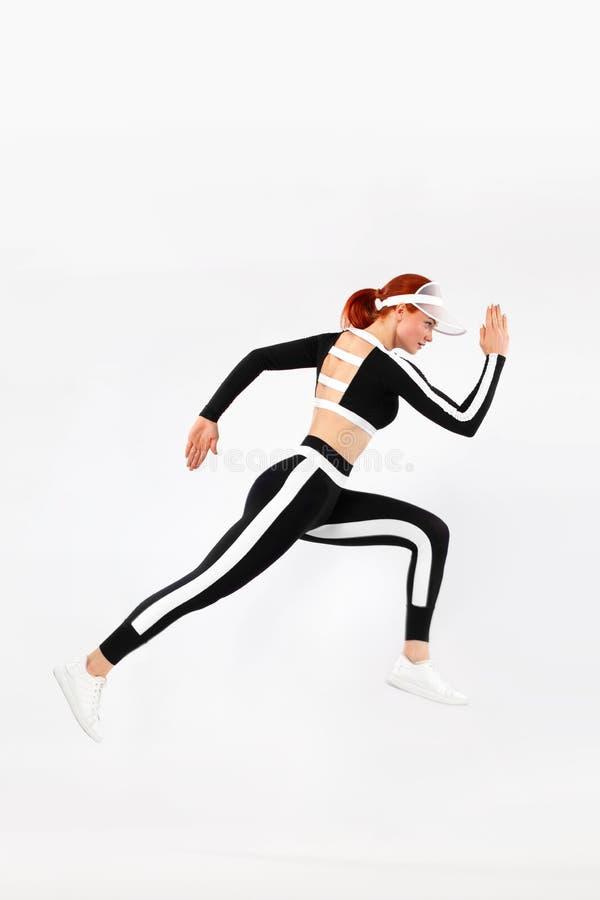 Ισχυρή αθλητική γυναίκα sprinter, τρέχοντας στο άσπρο υπόβαθρο που φορά sportswears Ικανότητα και αθλητικό κίνητρο δρομέας στοκ εικόνες με δικαίωμα ελεύθερης χρήσης