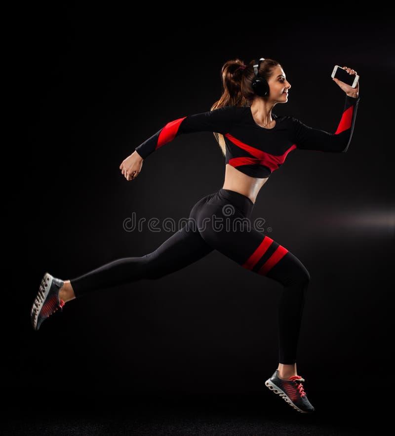 Ισχυρή αθλητική γυναίκα sprinter, τρέχοντας στο μαύρο υπόβαθρο που φορά sportswear και τα ακουστικά o στοκ εικόνες